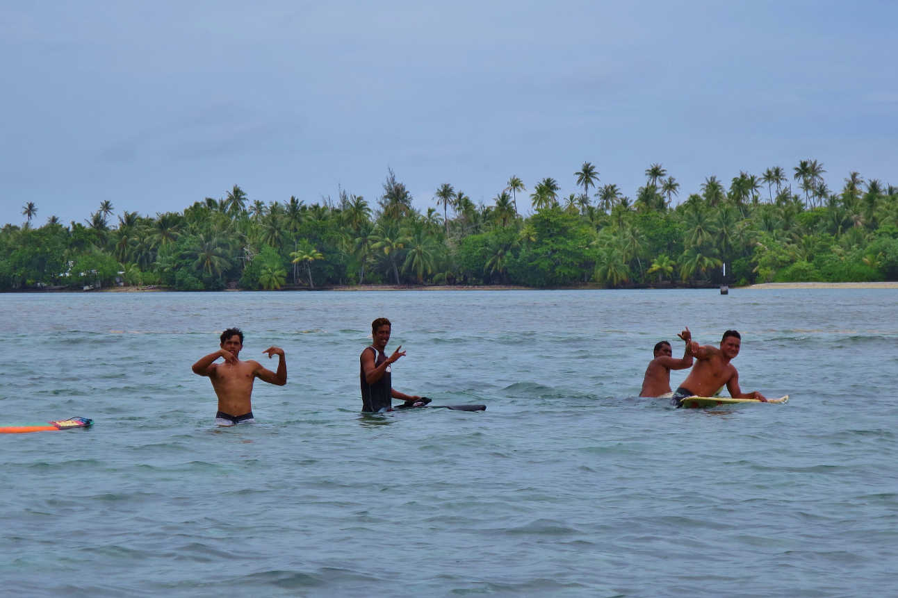 Dare-devil surfers heading out to Araara Pass which offers a dangerous reef break