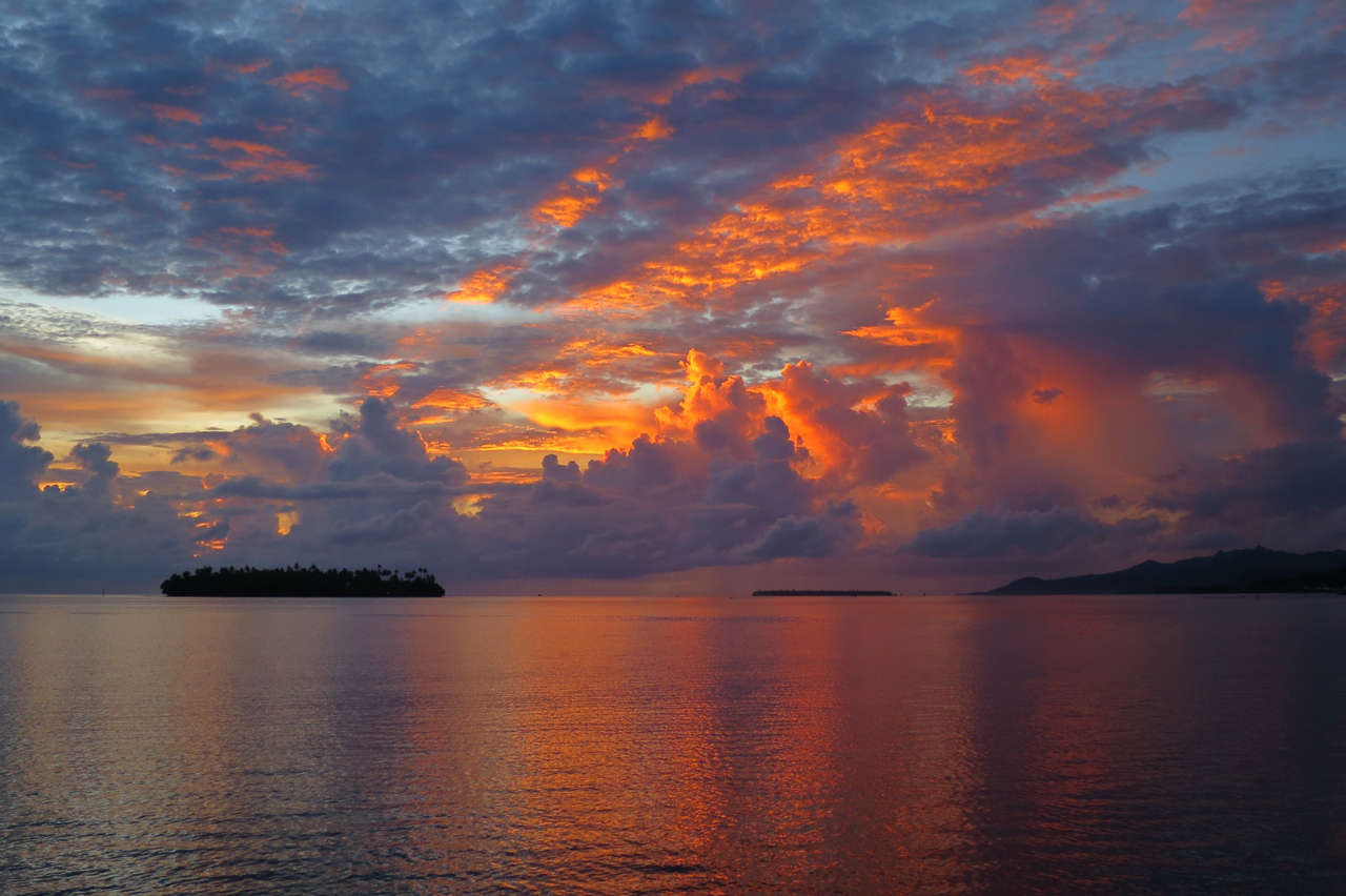 The fadin light paints a colorful sky during rainy season in Raiatea